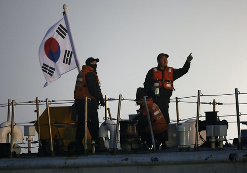 South Korean coastguard officers operate on vessel at site where capsized passenger ship Sewol sank in Jindo