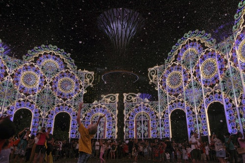 People play in fake snow made of foam as part of Christmas Wonderland at Gardens By The Bay in Singapore