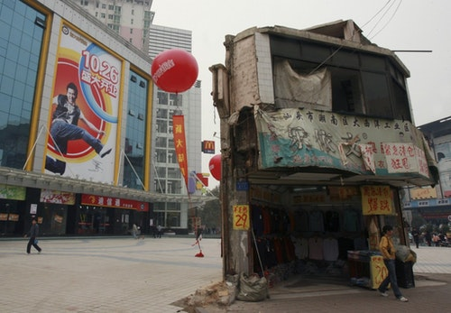 """A """"nail house"""", the last house in this area, stands on the square in front of a shopping mall in Changsha"""