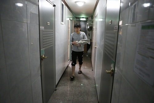 Kim Sa-myeong, 27, walks to the bathroom from his small room called a Goshiwon in one of the many private dorms that house students cramming for exams in Seoul December 13, 2012. There are 30,000 residents of a drab neighbourhood of the South Korean capital known as Exam Village, where people preparing for tests for low-level civil service jobs have gravitated for years. There is a growing sense of frustration among the young in a country where there are simply not enough jobs to go round, especially for graduates of less prestigious universities whose options are largely limited to the public sector. In Exam Village, or Goshichon in Korean, there were so many young people who wanted to cast early ballots last week that extra polling booths had to be brought in. Picture taken December 13, 2012. To match Analysis KOREA-ELECTION/YOUTH   REUTERS/Lee Jae-Won (SOUTH KOREA - Tags: POLITICS ELECTIONS EDUCATION) - RTR3BOU7