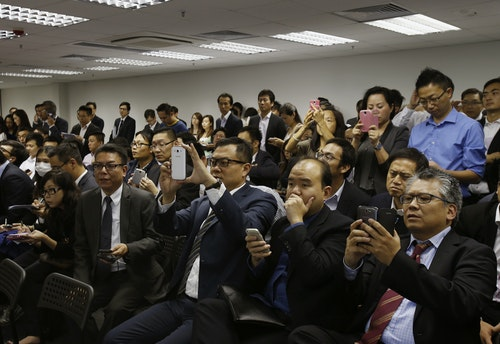 Property sales agents representing buyers record with smartphones during a draw on selling flats of a private residential estate in Hong Kong