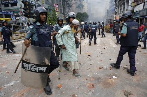 Police officers help a man cross a street during a clash with activists of Hefajat-e Islam in Dhaka