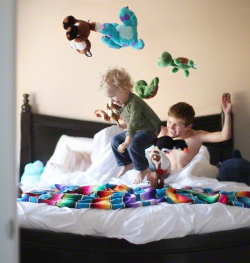 Boy jumping on brothers bed
