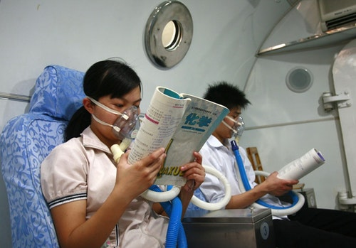 Students review the test material while inhaling pure oxygen at a hospital in Sichuan. Photo Credit: Reuters