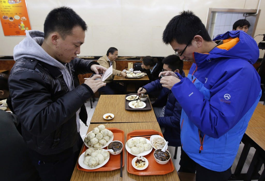 Diners take pictures of steamed buns which Chinese President Xi ate, at the Qing-Feng steamed buns restaurant in Beijing