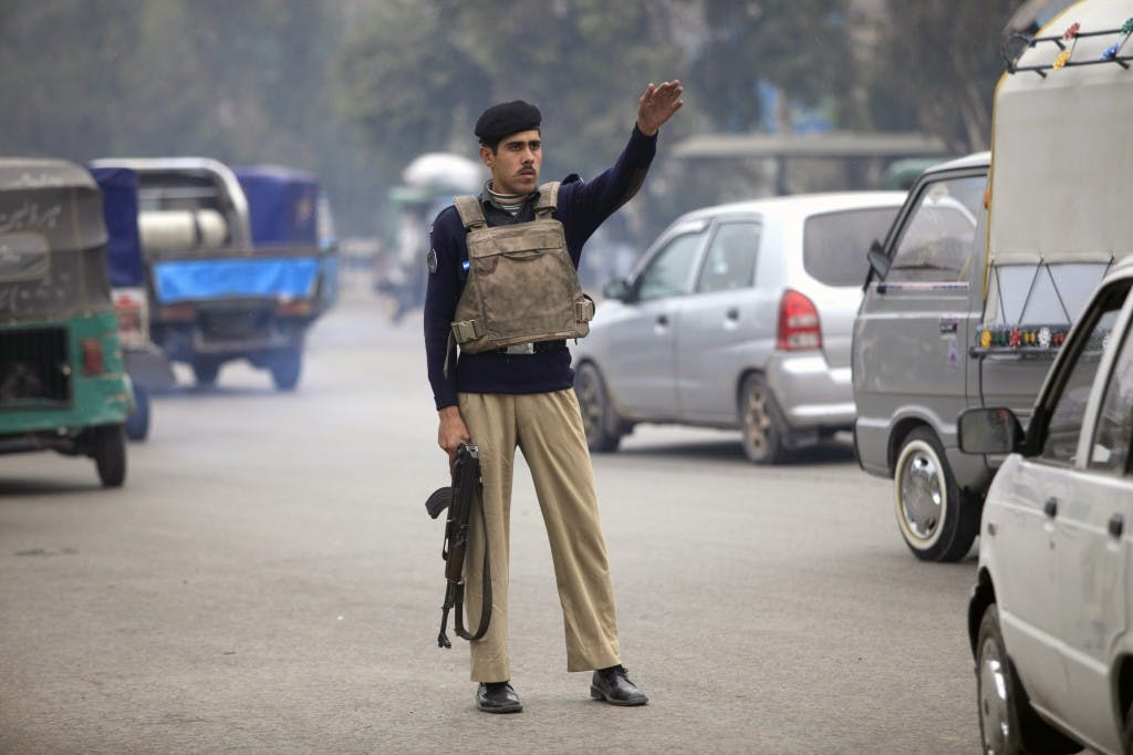 A policeman raises his hand to stop a car for a security check on a road in Peshawar