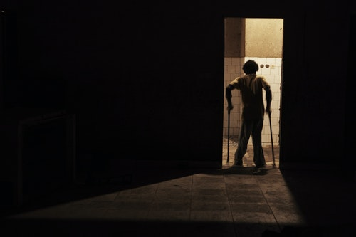 A youth suffering from polio walks through a doorway at the Stand Proud compound in Kinshasa