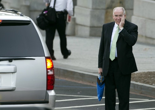 CIA Director John Brennan wipes his face as he waits for his SUV to take him from the West Wing of the White House in Washington