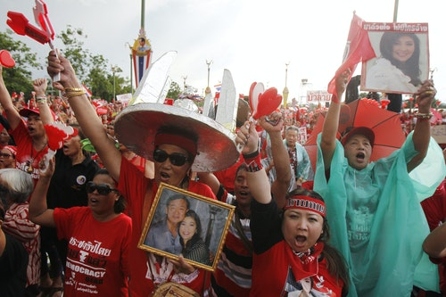 "A member of the pro-government ""red shirt"" group gestures while holding a picture of ousted Thai PM Yingluck Shinawatra and her brother Thaksin during a rally in Nakhon Pathom province"