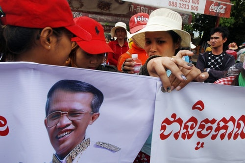 Cambodia garment workers hold banners with a portrait of Prime Minister Hun Sen while authority prevent them from reaching the prime minister's residence in Phnom Penh, Cambodia Tuesday, March 24, 2015. Workers marched Tuesday, urging Hun Sen to force their factory owner to follow the country's labor law and pay them the employment insurance after being fired. (AP Photo/Heng Sinith)