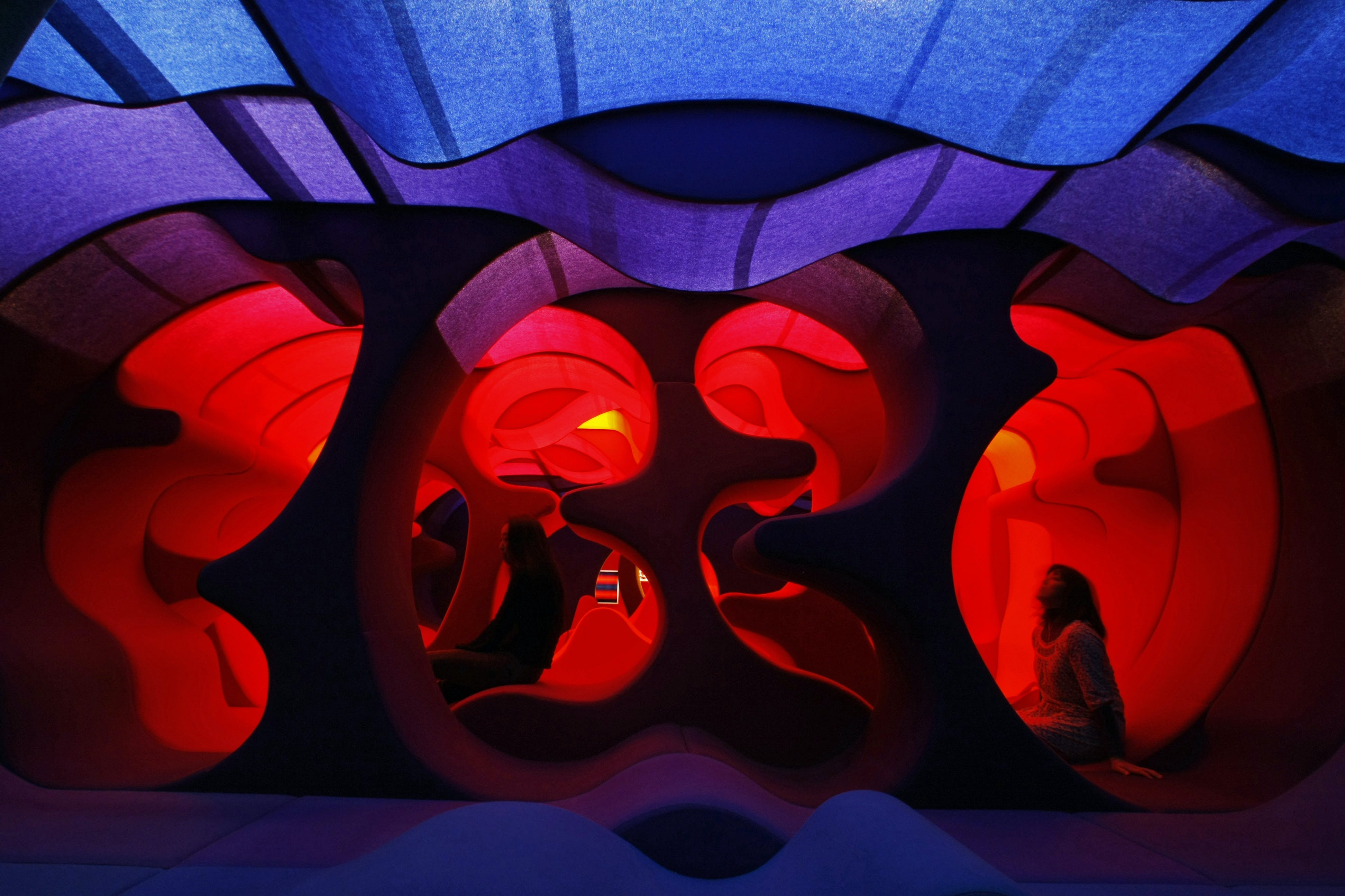 "A visitor sits on Verner Panton's "" Phantasy Landscape"" which is made of fabric, wood and foam rubber, at the Tokyo Opera city art gallery in Tokyo"