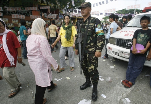 "An armed soldier stands guard as he secures a polling precinct during village, or ""barangay"", elections in Taguig City, Metro Manila October 25, 2010. Police said polling in nearly four percent of 42,000 villages failed due to delayed delivery of materials and violence. REUTERS/Cheryl Ravelo (PHILIPPINES - Tags: ELECTIONS POLITICS) - RTXTTB7"