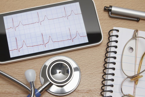 Technology use in healthcare. Smartphone displays an electrocardiogram, acoustic stethoscope, notepad, spectacles and pen on doctors office desk