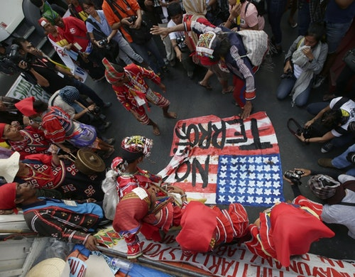"""Protesters, some of whom are indigenous peoples known as """"Lumad"""" dance as they stomp on a mock U.S. flag during a rally Monday, Nov. 24, 2014 at the U.S. Embassy in Manila to protest the presence of U.S. troops in southern Philippines under the """"Visiting Forces Agreement"""" entered into by the Philippines. The protesters embarked on a caravan from their communities in southern Philippines 13 days ago and are set to camp out in Manila until Dec.10 for the observance of UN Declaration of Human Rights. (AP Photo/Bullit Marquez)"""