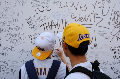 Fans sign a large banner congratulating Kobe Bryant before his last NBA basketball game, a contest against the Utah Jazz, outside Staples Center in downtown Los Angeles Wednesday, April 13, 2016. Many of Bryant's fans - even some of the adults - have never known Los Angeles without him. It's a feeling they're about to have to get used to as fans celebrate his final night as a Laker. (AP Photo/Richard Vogel)