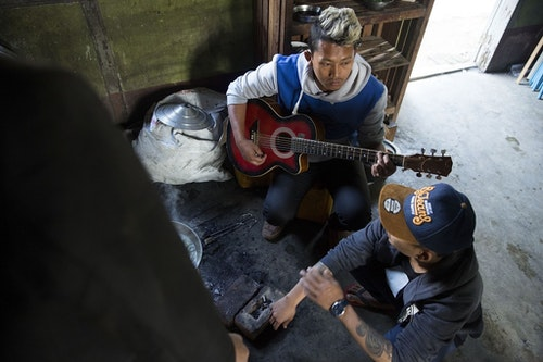 MYITKYINA, BURMA - JANUARY 26: A Pat Jasan member assigned to look after detainees plays guitar on January 26, 2016 in Myitkyina, Burma. Pat Jasan is a Christian anti-drug group in Kachin State claiming over 100,000 members. Dissatisfied with the government's response towards widespread heroin use and poppy growing, the religious organization has taken matters into their own hands, organizing patrols, raiding houses, detaining drug dealers and users, and clearing poppy fields. Their brand of vigilante justice has been labeled extreme with some chapters accused of publicly beating those involved in the drug trade. (Photo by Taylor Weidman/Getty Images)