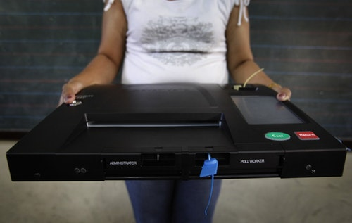 An official poses with the automated voting system at a school classroom which will be used as a voting centre in Manila May 6, 2010. The Philippines' automated voting system could throw up some problems in next week's election, but the last-minute replacement of faulty technology should prevent an outright failure, the election commission said on Thursday. REUTERS/Nicky Loh (PHILIPPINES - Tags: POLITICS ELECTIONS SCI TECH) - RTR2DJM1