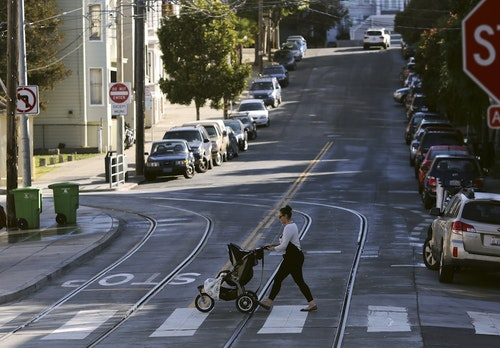 A woman walks with a child stroller across a pedestrian crossing, in San Francisco
