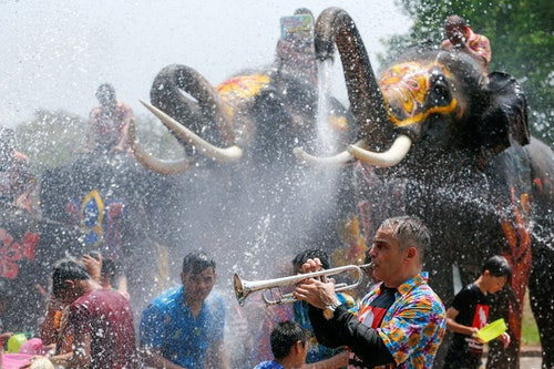 A man plays a trumpet while people are splashed by elephants with water during the celebration of the Songkran water festival in Thailand's Ayutthaya province