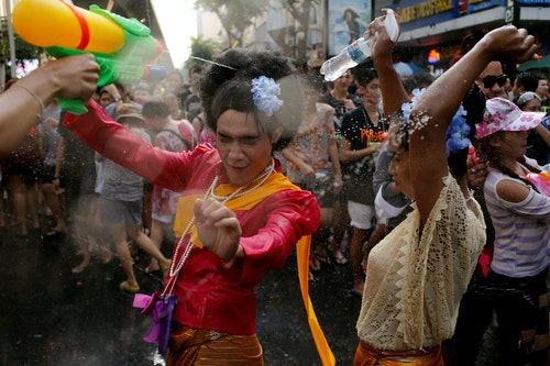 Revellers react during a water fight at Songkran Festival celebrations in Bangkok
