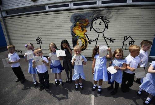 Reception class school children show off their drawings of a mural attributed to Banksy in Bristol