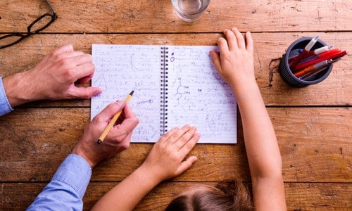 Unrecognizable father and son studying together, writing into notebook. Studio shot on wooden background. Flat lay.