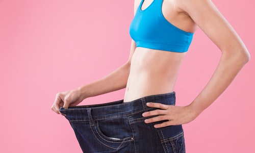 woman wear jeans and show weight loss on the pink background