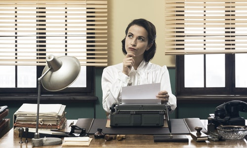 Pensive vintage woman with hand on chin, typing on typewriter and looking for inspiration