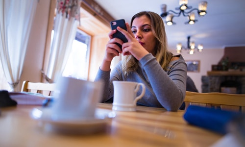 Smartphone addicted girl using device on a date or internet dating application concept — Photo by guteksk7