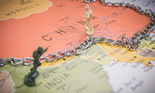 India and China borders symbolic photo with miniature soldier and a chain on borders world map