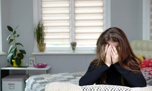 Photo of brunette girl with long dark hair in the room. She is very upset and sad. Sits on the sofa in front of the camera and is unhappy. Made in a residential apartment.
